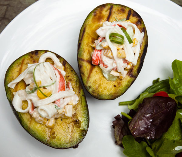 Grilled avocados stuffed with surimi salad, from Knuckle Salad